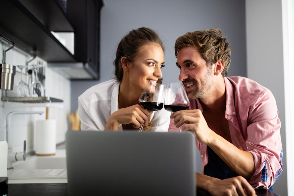 Young couple relaxing in kitchen with laptop and wine. Love, happiness, technology, people and fun concept.