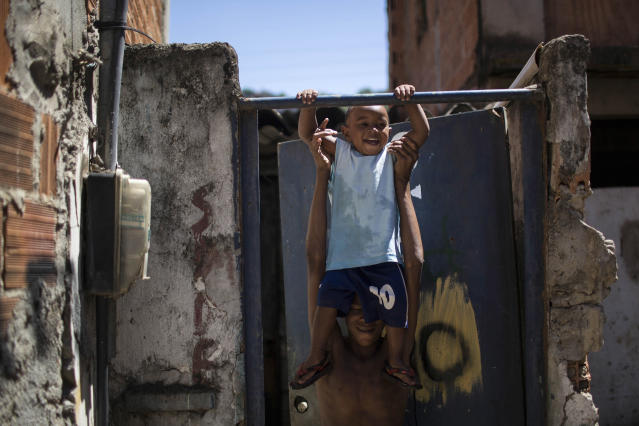In this Jan. 10, 2014 photo, a man plays with a toddler inside the Favela do Metro slum in Rio de Janeiro, Brazil. Some residents in this slum were evicted from their homes two years ago for the area to be renovated for this year's World Cup and 2016 Olympics, but people reoccupied the homes and are fighting to stay. (AP Photo/Felipe Dana)