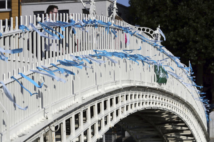 Blue ribbons are tied to Ha'Penny Bridge, Dublin to remember the victims of Catholic Church clerical sex abuse, ahead of the arrival of Pope Francis, in Dublin, Ireland, Saturday, Aug. 25, 2018. The pontiff is traveling to Ireland for a two-day visit on the occasion of the 2018 World Meeting of Families. (Aaron Chown//PA via AP)