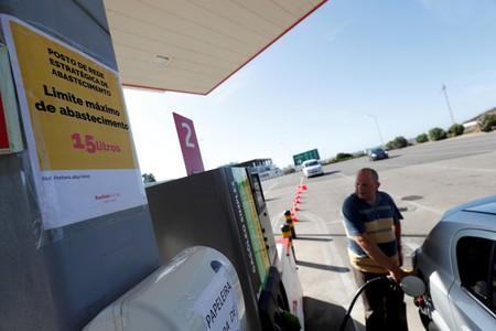 """A placard reading """"Maximum limit 15 litres per filling"""" is seen as a man fills up a car during a fuel strike, at a gas station in Lisbon"""
