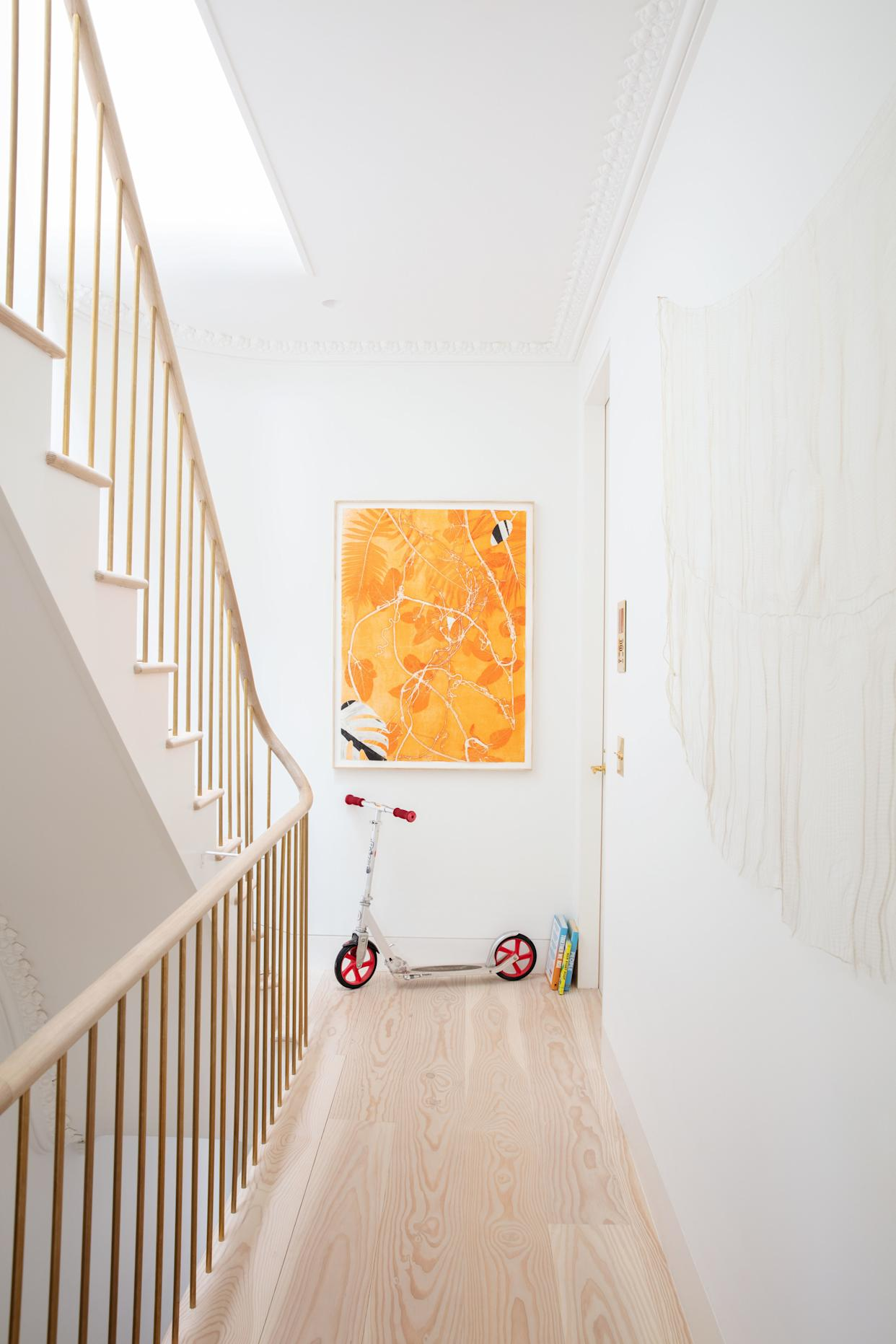 """<div class=""""caption""""> A staircase with a white oak railing rises through the home. Art by Luiz Zerbini and Paloma Bosquê is shown on the second-floor landing. </div>"""