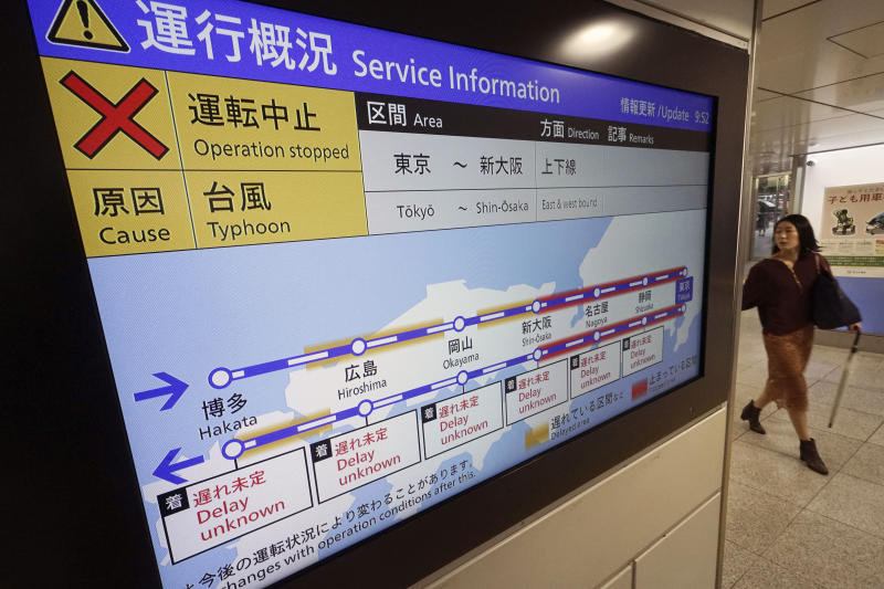 A passenger walks past an update notice on suspending operations of the Shinkansen or bullet train on Oct. 12-13 due to Typhoon Hagibis, at Tokyo Station in Tokyo Saturday, Oct. 12, 2019. Tokyo and surrounding areas braced for a powerful typhoon forecast as the worst in six decades, with streets and trains stations unusually quiet Saturday as rain poured over the city. (AP Photo/Eugene Hoshiko)