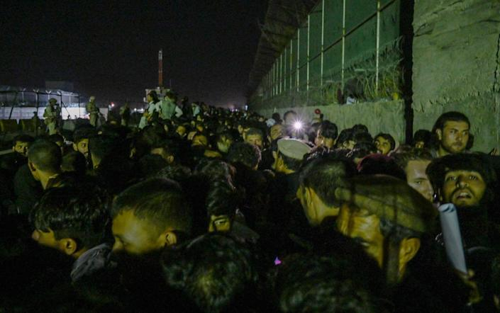 Afghans wait outside the foreign military-controlled part of the airport in Kabul on Sunday night, hoping to flee the country - WAKIL KOHSAR/AFP