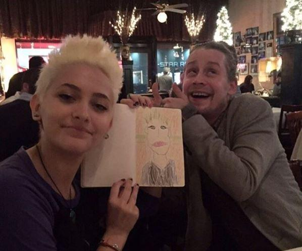 "<p>In October, Paris shared a throwback of a dinner date she had with Mac, who knows what it's like to <a href=""https://www.yahoo.com/celebrity/macaulay-culkin-addresses-drug-rumors-222400385.html"" data-ylk=""slk:make rumors for just living"" class=""link rapid-noclick-resp"">make rumors for just living</a>. ""Throwback to when the best godfather ever drew me,"" she wrote alongside the pic, in which she's holding up a portrait of herself as Culkin gives it two thumbs up. They're both true characters — and it's good they have each other. (Photo: Paris Jackson via Twitter) </p>"