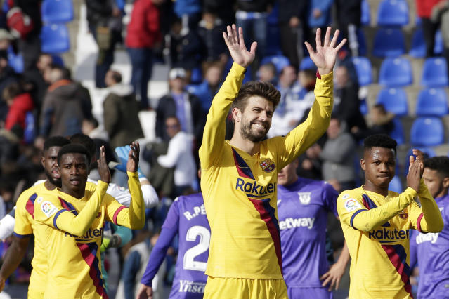 Barcelona's Gerard Pique, center, Barcelona's Ansu Fati, right, and Barcelona's Junior Firpo applaud fans at the end of the Spanish La Liga soccer match between Leganes and FC Barcelona at the Butarque stadium in Madrid, Spain, Saturday Nov. 23, 2019. Barcelona won 2-1. (AP Photo/Paul White)
