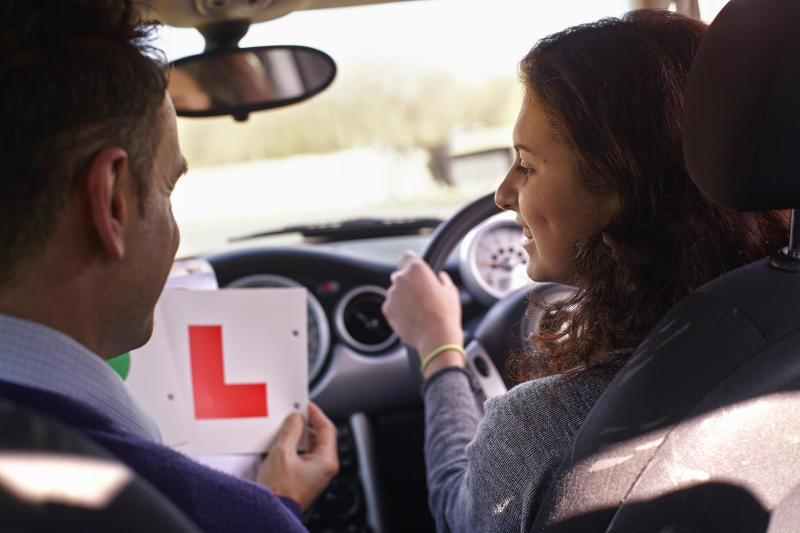 Driving instructor showing Learner Plate to learner driver