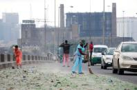 Cars drive as people clean the streets in Lagos