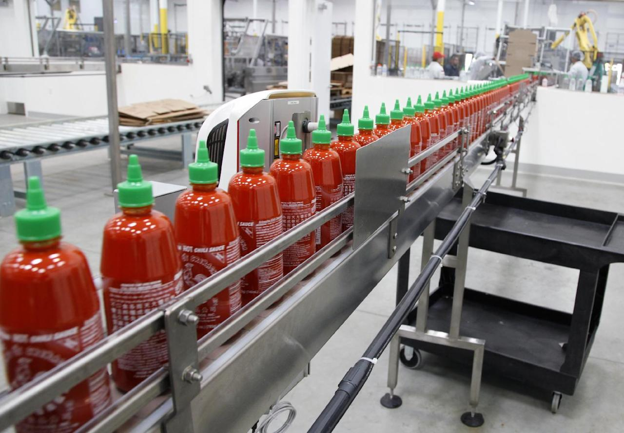 This Tuesday Oct. 29, 2013 photo shows Sriracha chili sauce moves along a production line during at the Huy Fong Foods factory in Irwindale, Calif., on Tuesday, Oct 29, 2013. The maker of Sriracha hot sauce is under fire for allegedly fouling the air around its Southern California production site. The city of Irwindale filed a lawsuit in Los Angeles Superior Court Monday asking a judge to stop production at the Huy Fong Foods factory, claiming the chili odor emanating from the facility is a public nuisance. (AP Photo/Nick Ut)