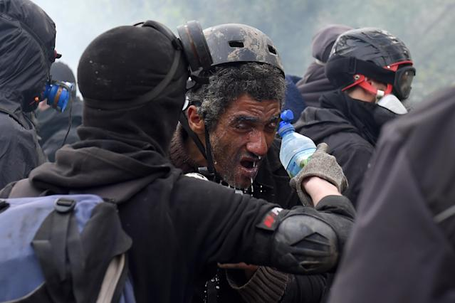 <p>A man pours water on a fellow protester's face as riot forces use tear gas when clashes erupt on April 10, 2018 during a police operation to raze the decade-old camp known as ZAD (Zone a Defendre – Zone to defend) at Notre-Dame-des-Landes, near the western city of Nantes, and evict the last of the protesters who had refused to leave despite the government agreeing to ditch a proposed airport. (Photo: Guillaume Souvant/AFP/Getty Images) </p>