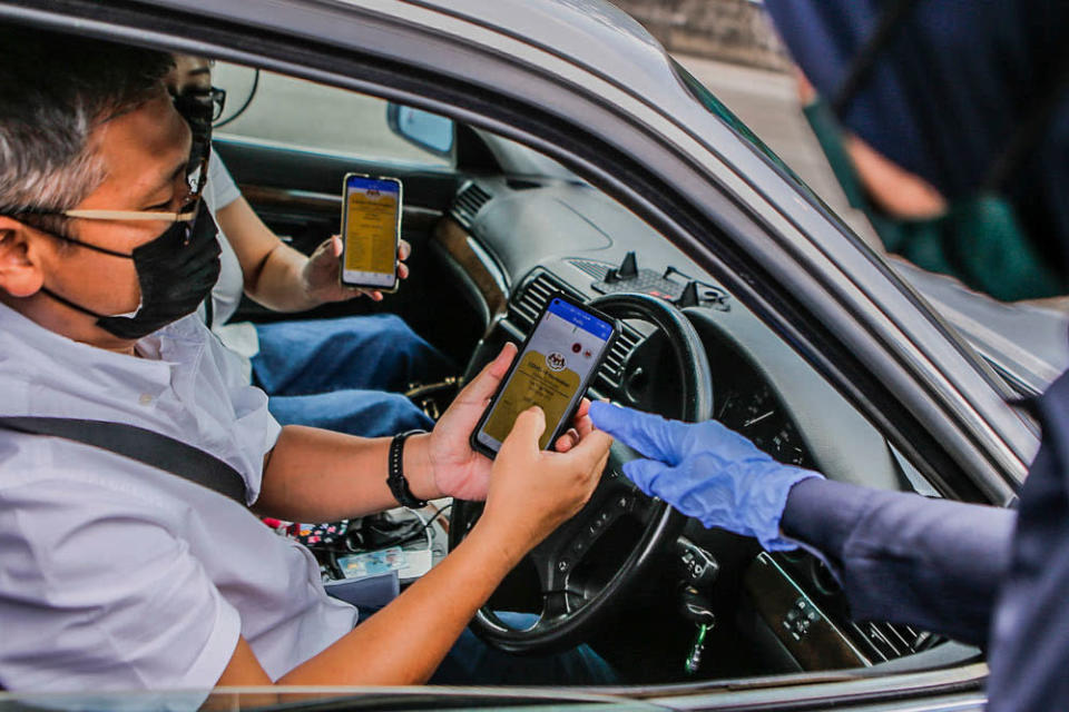 A man and his passenger show their Covid-19 digital vaccination certificate to police at the Plaza Bentong roadblock August 11, 2021. ― Picture by Hari Anggara