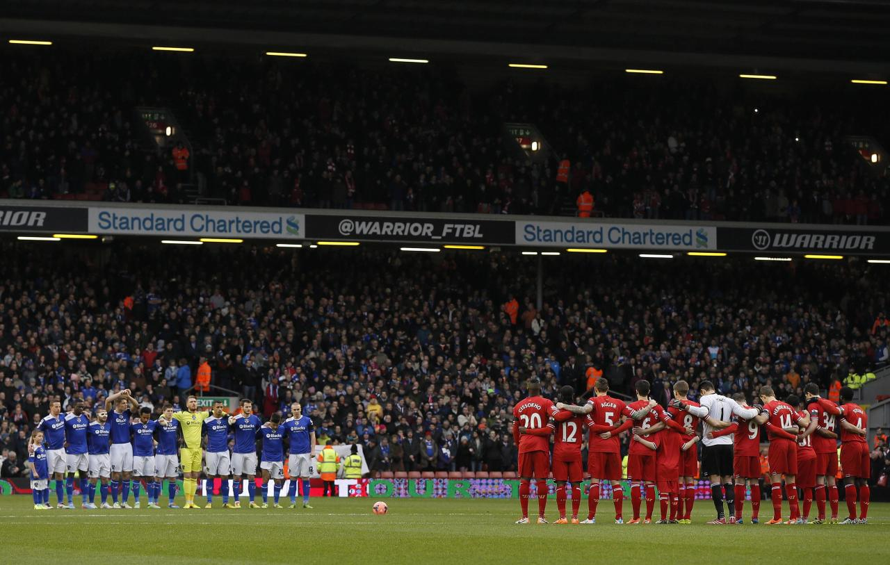 Oldham Athletic players (L) and Liverpool players stand during a minute's silence in honour of former Oldham Athletic and Liverpool player Wayne Harrison and Portuguese great Eusebio during their FA Cup third round soccer match at Anfield in Liverpool January 5, 2014. REUTERS/Phil Noble (BRITAIN - Tags: SPORT SOCCER)