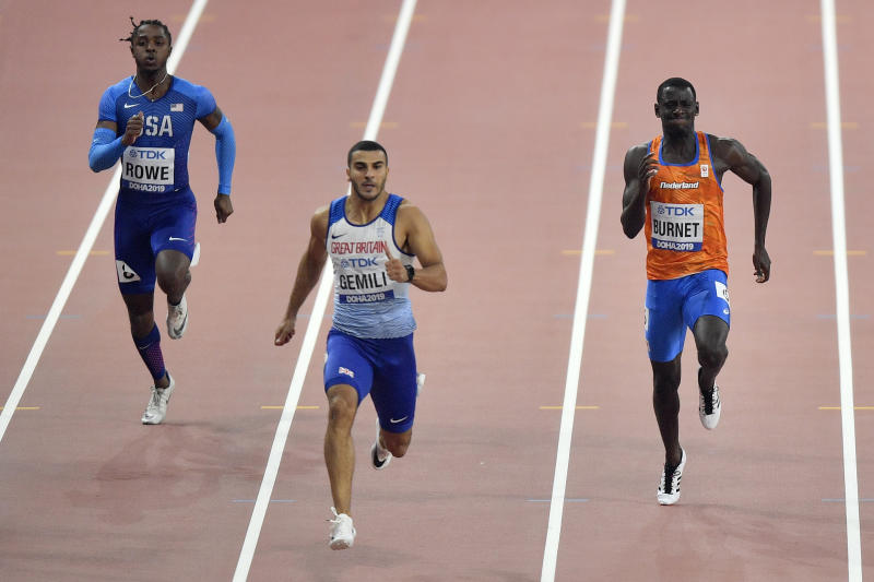 Rodney Rowe, of the United States, Adam Gemili, of Great Britain, and Taymir Burnet, of the Netherlands,, from left to right, compete in the men's 200 meter heats during the World Athletics Championships in Doha, Qatar, Sunday, Sept. 29, 2019. (AP Photo/Martin Meissner)