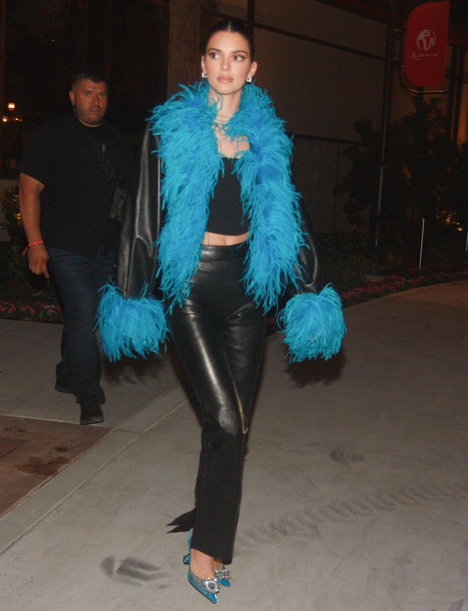<p>Kendall Jenner accessorizes her leather outfit with a blue feather boa while on her way to the Flamingo hotel in Las Vegas on June 25.</p>