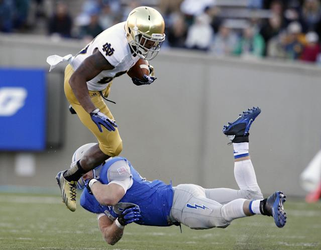 Notre Dame running back Tarean Folston, top, is tripped by Air Force linebacker Joey Nichol after a short gain in the third quarter of Notre Dame's 45-20 victory in an NCAA college football game in Air Force Academy, Colo., Saturday, Oct. 26, 2013. (AP Photo/David Zalubowski)