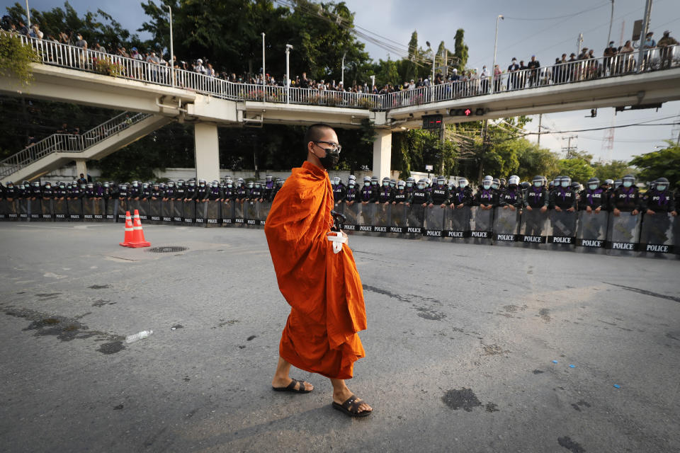A monk walk pass police blocking protesters in a main intersection as he returns to his temple near the Parliament in Bangkok, Tuesday, Nov. 17, 2020. Thailand's political battleground shifted to the country's Parliament Tuesday, where lawmakers are considering proposals to amend the country's constitution, one of the core demands of the student-led pro-democracy movement. (AP Photo/Sakchai Lalit)