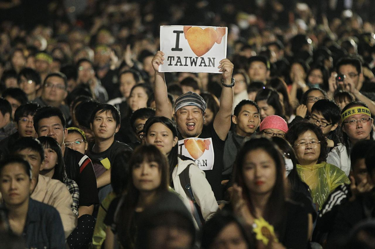 A protester displays a banner supporting Taiwan during a massive protest over the controversial China Taiwan trade pact in front of the Presidential Building in Taipei, Taiwan, Sunday, March 30, 2014. Over a hundred thousand protesters gathered in the rally against the island's rapidly developing ties with the communist mainland. (AP Photo/Wally Santana)