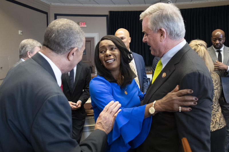 Rep. William Lacy Clay, D-Mo., left, and Rep. David Trone, D-Md., right, talk with Judy Pace Flood, after a news conference as they call for the late Curt Flood to be inducted into the Baseball Hall of Fame, on Capitol Hill, Thursday, Feb. 27, 2020 in Washington. (AP Photo/Alex Brandon)