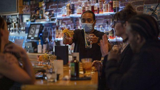 PHOTO: A bartender wearing a protective mask serves drinks in a bar in San Francisco, May 6, 2021.  (David Paul Morris/Bloomberg via Getty Images)