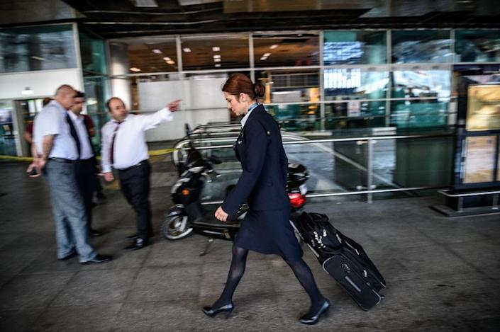 An air stewardess walks past a cordoned-off area outside Ataturk airport on June 29, 2016 (AFP Photo/Ozan Kose)