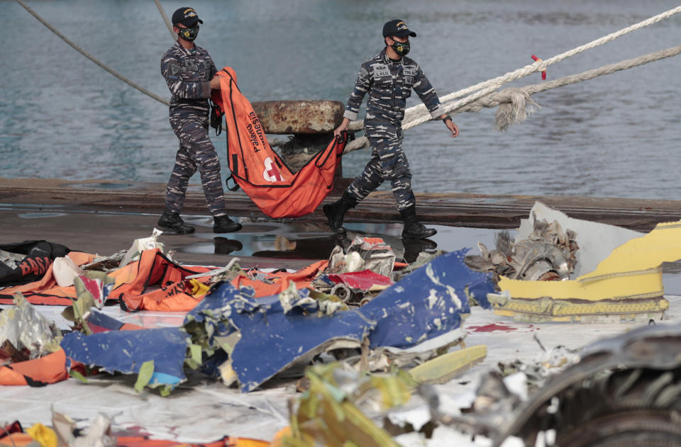 Navy sailors carry a body bag containing the recovered remains of victims of the Sriwijaya Air flight SJ-182 that crashed on Jan. 9, at Tanjung Priok Port in Jakarta, Indonesia, Thursday, Jan. 21, 2021. Indonesian authorities on Thursday ended the search for the wreckage of the plane that nose-dived into the sea, killing all of its passengers on board. (AP Photo/Dita Alangkara)