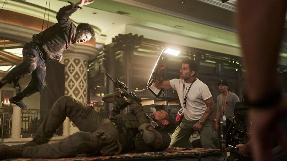 Zack Snyder films a zombie on wires in a behind-the-scenes shot from Army of the Dead.