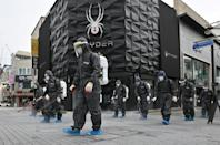 South Korean health officials from Bupyeong-gu Office wear protective gearto spray disinfectant at a shopping district in Incheon