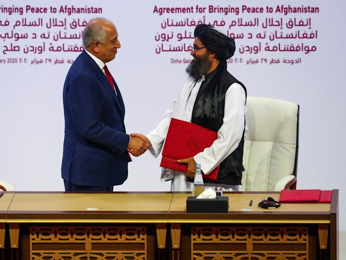 Mullah Abdul Ghani Baradar, the leader of the Taliban delegation, and Zalmay Khalilzad, U.S. envoy for peace in Afghanistan, shake hands after signing an agreement at a ceremony between members of Afghanistan's Taliban and the U.S. in Doha, Qatar February 29, 2020. REUTERS/Ibraheem al Omari