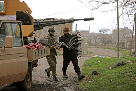 Turkish-backed Free Syrian Army fighters hold an ammunition belt near the city of Afrin