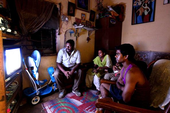 Ravi Das, his wife Geeta Das and cousin Rahul Das watch the London 2012 Olympic Opening Ceremony at Ravis Das' home in Sobroto Park on July 28, 2012 in Delhi, India.  (Photo by Graham Crouch/Getty Images)