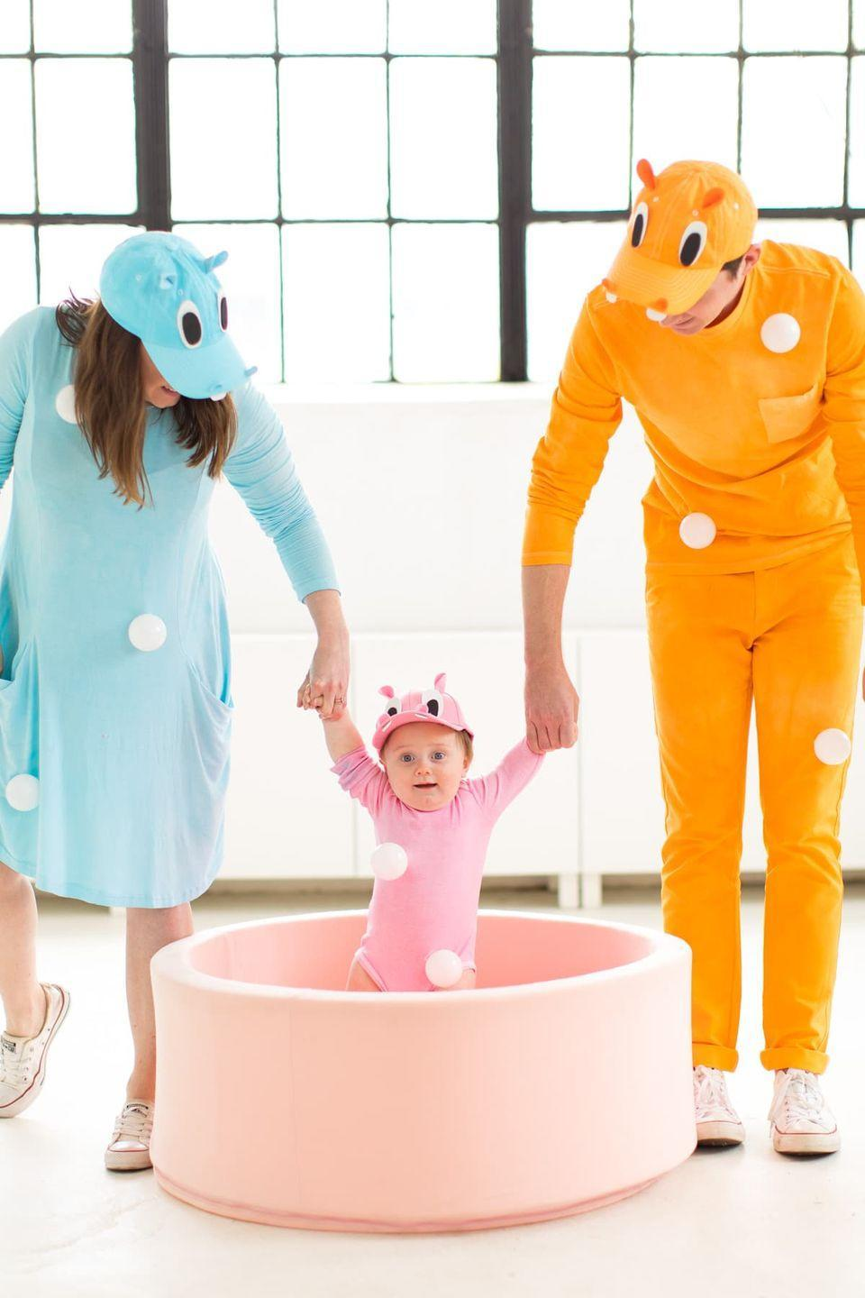 """<p>Re-create the classic game in an absolutely adorable way. How cute will your little one look dressed up as a hippo?</p><p><strong>Get the tutorial <a href=""""https://sugarandcloth.com/our-family-diy-hungry-hippos-costume-idea/"""" rel=""""nofollow noopener"""" target=""""_blank"""" data-ylk=""""slk:Sugar & Cloth"""" class=""""link rapid-noclick-resp"""">Sugar & Cloth</a>.</strong></p><p><strong><a class=""""link rapid-noclick-resp"""" href=""""https://www.amazon.com/Lightaling-100pcs-White-Plastic-Phthalate/dp/B07DWYG2CS/?tag=syn-yahoo-20&ascsubtag=%5Bartid%7C10050.g.29074815%5Bsrc%7Cyahoo-us"""" rel=""""nofollow noopener"""" target=""""_blank"""" data-ylk=""""slk:SHOP PLASTIC BALLS"""">SHOP PLASTIC BALLS</a><br></strong></p>"""