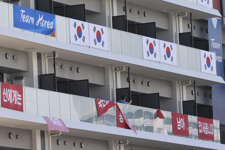 """FILE - In this July 17, 2021, file photo, banners with the words """"I still have the support of 50 million Korean people,"""" are removed from balconies at the the Olympic athletes' village in Tokyo. South Korea removed the banners that the IOC ruled to be provocative, Seoul said it received an IOC promise that the displaying of the """"rising sun"""" flag would also be banned at stadiums and other Olympic venues. (Jin Sung-chul/Yonhap via AP, File)"""