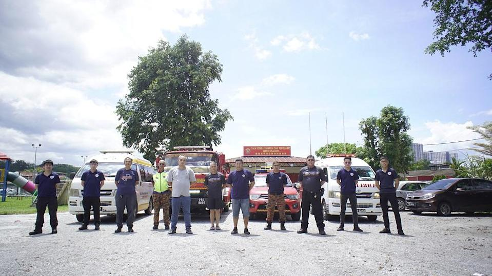 The members of the Pasukan Bomba Sukarela Kepong (PBSK) pose for a photograph in front of their station. — Picture by Arif Zikri