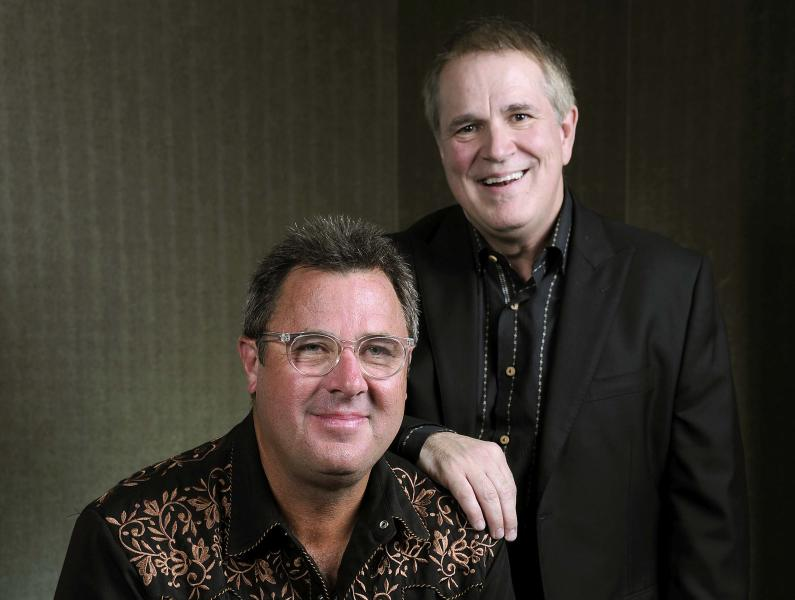 """This Saturday, July 27, 2013 photo shows Vince Gill, left, and Paul Franklin posing at the Grand Ole Opry in Nashville, Tenn. Gill and Franklin released their latest album """"Bakersfield,"""" on July 30. (Photo by Donn Jones/Invision/AP)"""