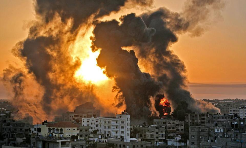 A fire rages at sunrise in Khan Yunis following an Israeli airstrike on targets in the southern Gaza strip, early on May 12.
