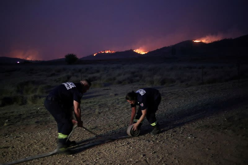 FILE PHOTO: Personnel from Fire and Rescue NSW work as a bushfire approaches a home in Bredbo