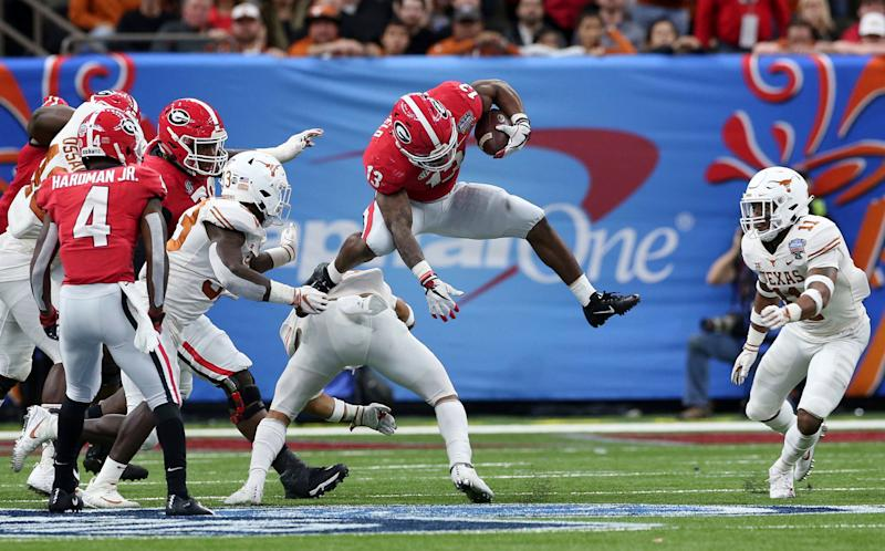 Georgia running back Elijah Holyfield (13) hurdles a Texas defender during the second half of the Sugar Bowl NCAA college football game in New Orleans, Tuesday, Jan. 1, 2019. (AP Photo/Rusty Costanza)