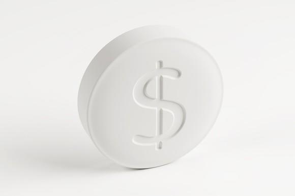 A white generic prescription drug tablet with a dollar sign stamped on it.