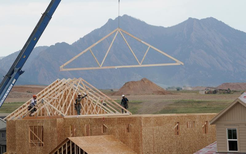 FILE PHOTO: Workers install roof trusses onto a new house in Arvada