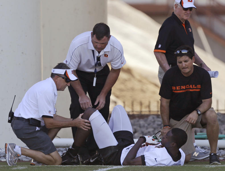 Cincinnati Bengals wide receiver A.J. Green has his knee checked by head trainer Paul Sparling, left, after he injured it trying to catch a pass during practice at the NFL football team's training camp, Thursday, July 25, 2013, in Cincinnati. Green twisted his left knee. Coach Marvin Lewis said the injury doesn't appear to be serious. (AP Photo/Al Behrman)