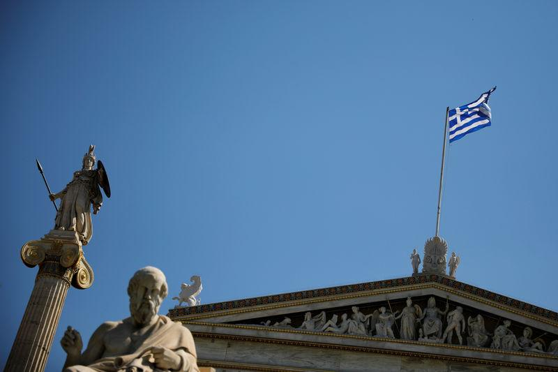 A Greek national flag flies atop the Athens Academy next to the statues of ancient goddess Athena and Greek philosopher Plato in Athens