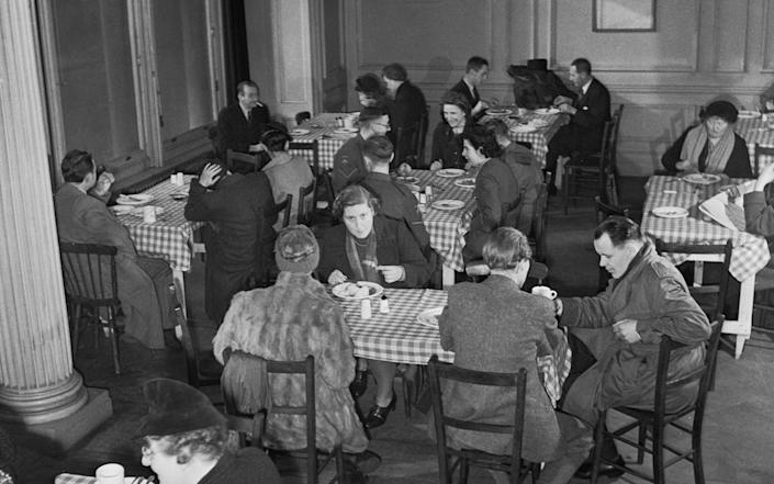 Miss Pauline Craske (centre, facing camera) enjoys a meal at a British Restaurant in London, 1943. - Getty Images/Imperial War Museums