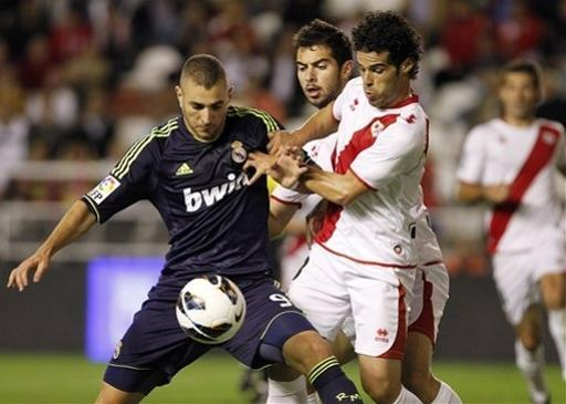 Real Madrid's Karim Benzema from France, left, vies for the ball with Rayo Vallecano's Jose Manuel Casado, right, during a Spanish La Liga soccer match at the Vallecas stadium in Madrid, Spain, Monday, Sept. 24, 2012. (AP Photo/Andres Kudacki)