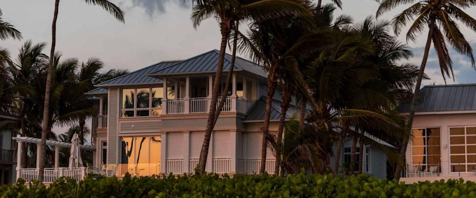Coast house beachfront waterfront vacation home, house during evening sunset with nobody in Florida, gulf of mexico, storm weather and wind palm trees