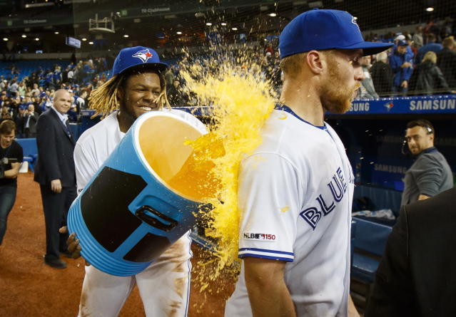 Toronto Blue Jays' Vladimir Guerrero Jr. douses teammate Brandon Drury after Drury hit a walkoff home run to defeat the Oakland Athletics during the ninth inning of baseball game action in Toronto, Friday, April 26, 2019. (Mark Blinch/The Canadian Press via AP)