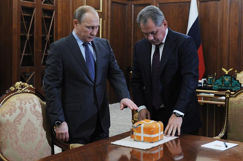 Russian President Vladimir Putin (L) and Defence Minister Sergei Shoigu examine the flight recorder from the Russian Sukhoi Su-24 bomber which was shot down by a Turkish jet, on December 8, 2015