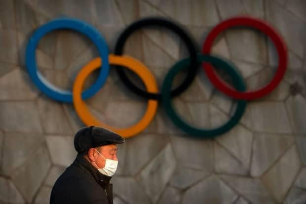 A man wearing a face mask to protect against the coronavirus walks past the Olympic rings on the exterior of the National Stadium, also known as the Bird's Nest, which will be a venue for the upcoming 2022 Winter Olympics, in Beijing, Tuesday, Feb. 2, 2021. A motion passed by the House of Commons today calls on the government to lobby for relocation of the games out of China due to the country's human rights record.