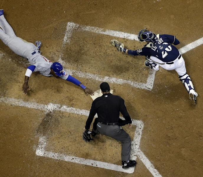 Chicago Cubs' Junior Lake, left, slides safely past Milwaukee Brewers catcher Jonathan Lucroy, right, during the seventh inning of a baseball game Tuesday, Sept. 17, 2013, in Milwaukee. (AP Photo/Morry Gash)