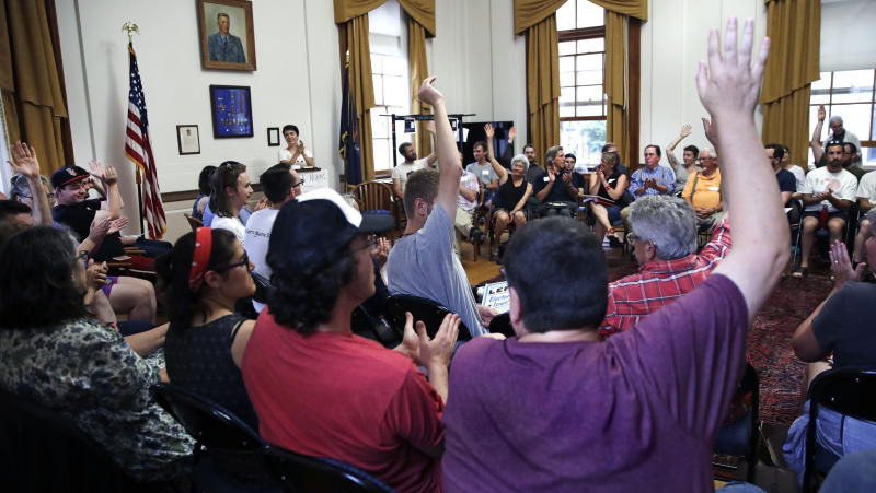 First time guests raise their hands during introductions during a meeting with members of the Southern Maine Democratic Socialists of America in Portland, Maine, Monday, July 16, 2018. On the ground in dozens of states, there is new evidence that democratic socialism is taking hold as a significant force in Democratic politics. (AP Photo/Charles Krupa)