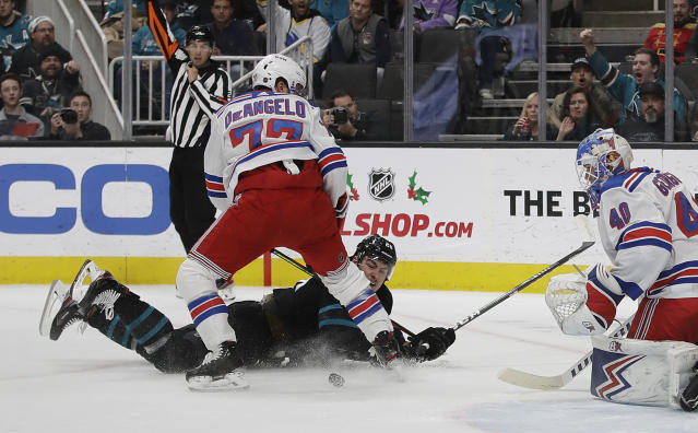 San Jose Sharks' Timo Meier, on ice, watches his shot against New York Rangers goalie Alexandar Georgiev, right, as Rangers' Tony DeAngelo (77) also defends during the first period of an NHL hockey game Thursday, Dec. 12, 2019, in San Jose, Calif. (AP Photo/Ben Margot)