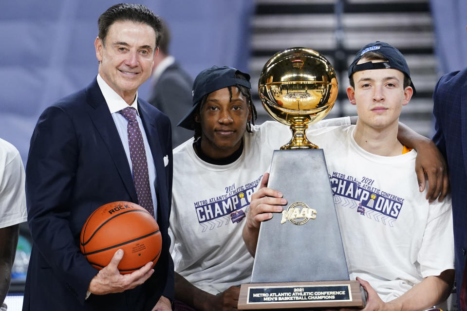 Iona head coach Rick Pitino, from left, Isaiah Ross and Dylan van Eyck pose with the trophy after winning an NCAA college basketball game against Fairfield during the finals of the Metro Atlantic Athletic Conference tournament, Saturday, March 13, 2021, in Atlantic City, N.J. (AP Photo/Matt Slocum)